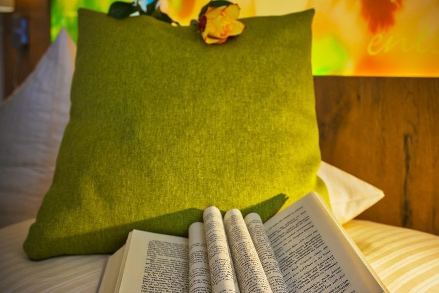 Entspannung für Leseratten mit Buch auf dem Bett im Hotel Sonnengarten Bad Wörishofen
